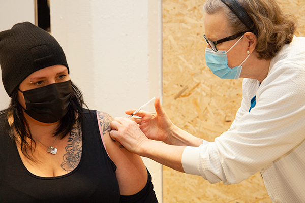 Nurse vaccinating a woman.