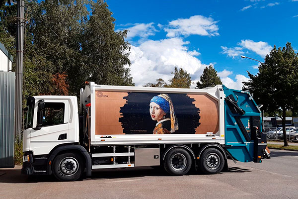 Girl With a Cardboard Earring, an artwork by Jirka Väätäinen on a waste collection truck