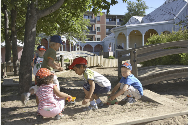 Children playing in a sandbox on the yard of daycare centre Pikkuprinssi.