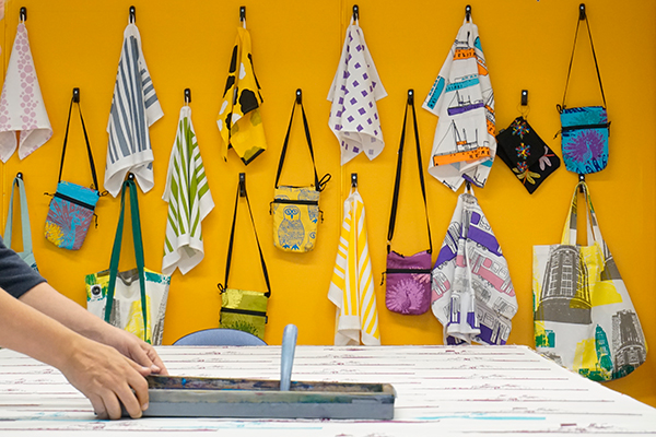 colourful towels hanging on a yellow wall