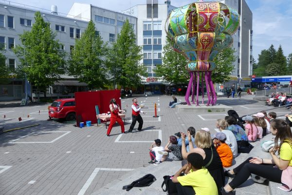 People enjoying outdoor programming in summer on Kannelmäki's Sitratori square.